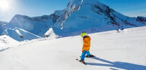 child skiing down slopes